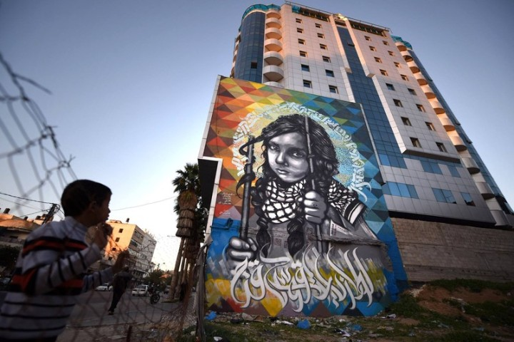 """Besieged Childhood,"" a mural co-created by Belal Khaled, on a Gaza City tower. (Abed Zagout)"
